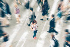 Une femme utilise un téléphone intelligent en traversant la rue au milieu d'une foule. Vue en plongée.